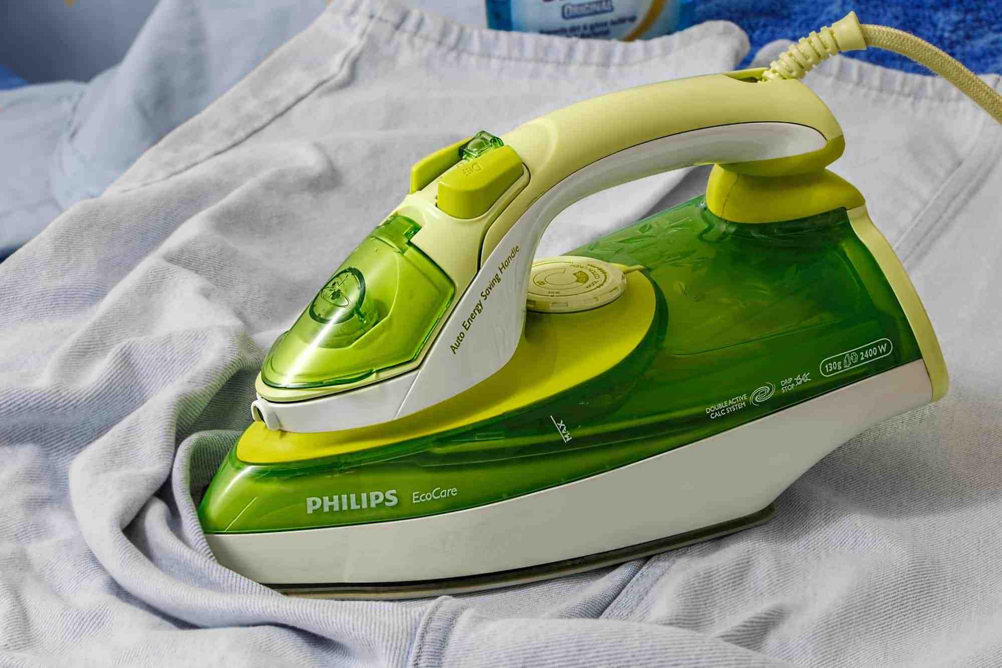 A green steam iron flat-side down on creased white fabric